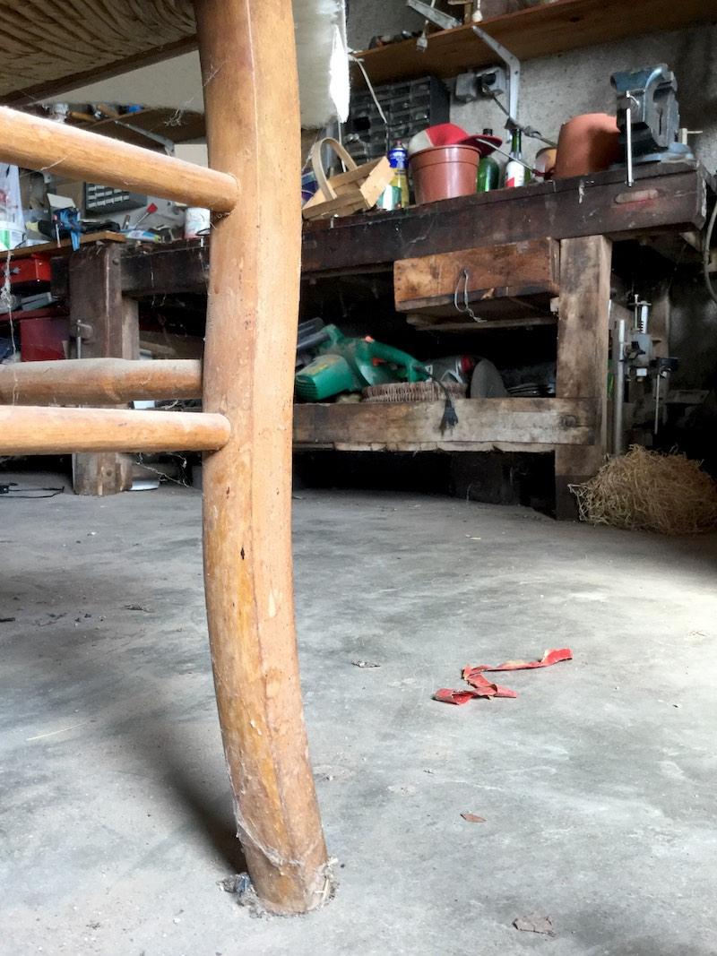 Vue de l'atelier avec un pied de chaise au premier plan et l'établi au fond