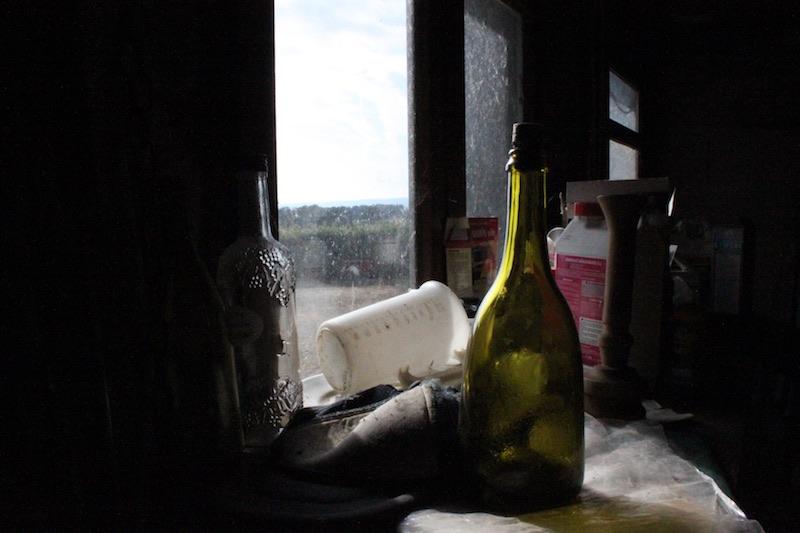 Atelier avec bouteille vide au premier plan et fenêtre floue en arrière-plan
